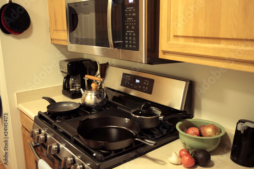 Modern stainless steel gas stove oven with cookware in a home.