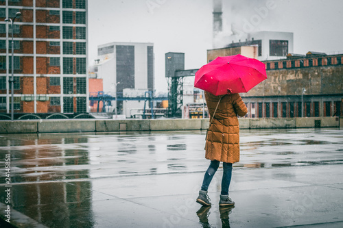 fototapeta na lodówkę Woman with red umbrella standing in city during snowing