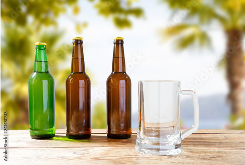 Foto op Canvas Bier / Cider empty goblet and bottles of beer on wooden table on blurred vacation background, craft cider and beer