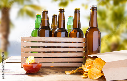 Foto op Canvas Bier / Cider potato chips and beer bottles on wooden table