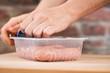 Frau nimmt verpackte rohe frische grobe Bratwurst aus Fleisch Plastik Verpackung