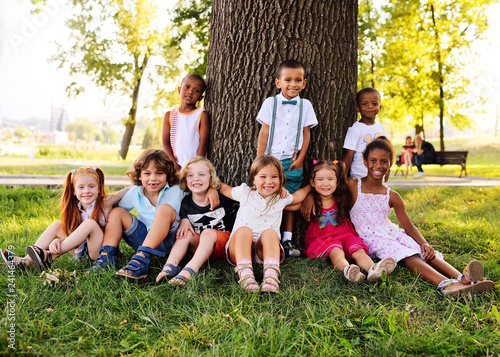 Fotografia  a group of children of different racial and ethnic types sit together under a big tree in the Park on the grass and smile