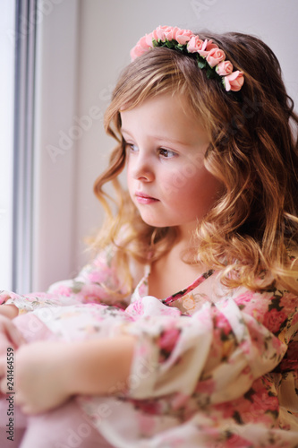 d01ddce91d9e beautiful little girl the child in a smart dress sits on the windowsill,  looks out