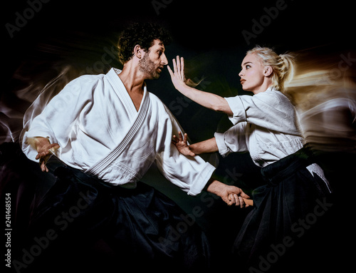 Photo two bodokas fighters man and woman practicing Aikido studio shot isolated on bla