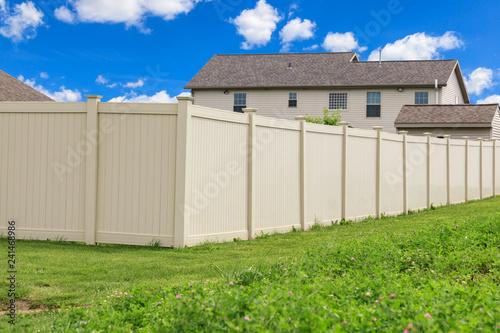 Fotografia Tan colored vinyl fence surrounding a homes backyard