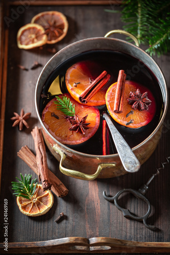Hot and sweet mulled red wine on rustic table