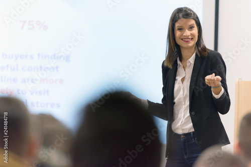 Fotografia Pretty young businesswoman, teacher or mentor coach speaking to young students in audience at training seminar, female business leader speaker talking at meeting