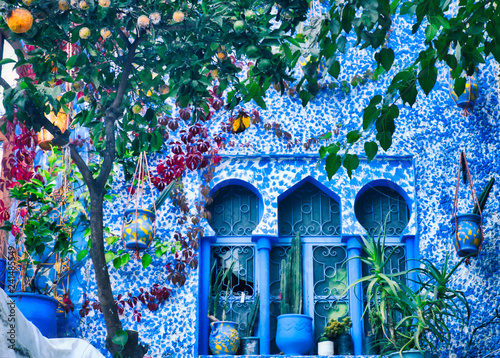 Poster Maroc Arab style windows decorated with pots and a tangerine tree. Image taken in Chefchaouen, a beautiful village in northern Morocco