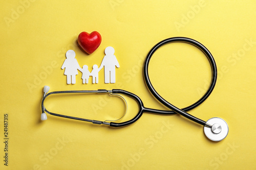Fotomural  Flat lay composition with heart, stethoscope and paper silhouette of family on color background
