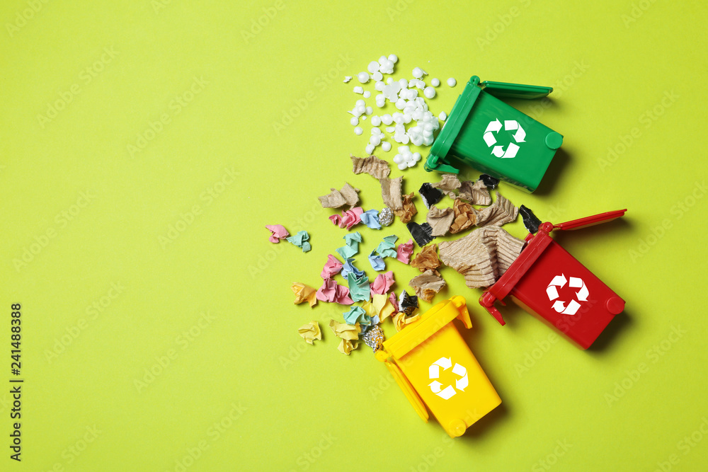 Fototapeta Trash bins and different garbage on color background, top view with space for text. Waste recycling concept