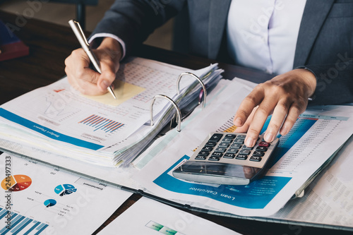 Fototapeta Business woman using calculator and laptop for do math finance on wooden desk in office and business working background, tax, accounting, statistics and analytic research concept obraz