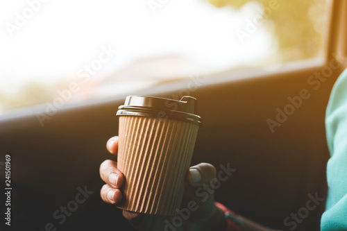 A man holding a cup of coffee in the car.