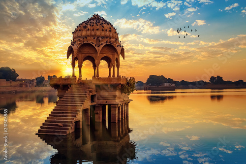 Obraz Ancient architecture ruins at Gadi Sagar (Gadisar) lake Jaipur Rajasthan at sunrise with vibrant moody sky.  - fototapety do salonu