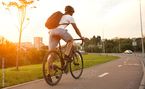 In de dag Fietsen The young guy in casual clothes is cycling on the road in the evening city