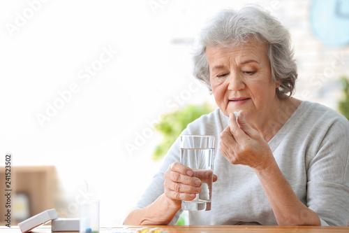 Obraz Elderly woman taking pill at home - fototapety do salonu