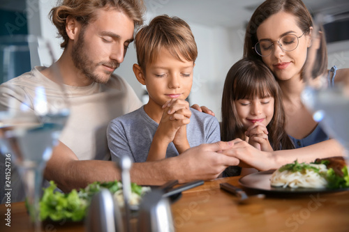 Family praying before meal at home