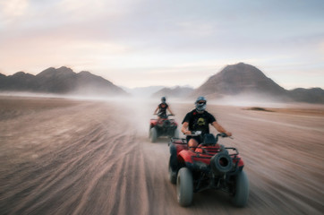 Buggy and ATV quads races in Sinai desert at sunset. Egyptian landscape with off-road vehicles and dust dirt road. Sharm el Sheikh, Egypt. Defocused motion blur