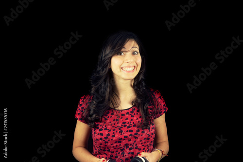 A cute young woman smiling in a goofy way. Black background. Tapéta, Fotótapéta