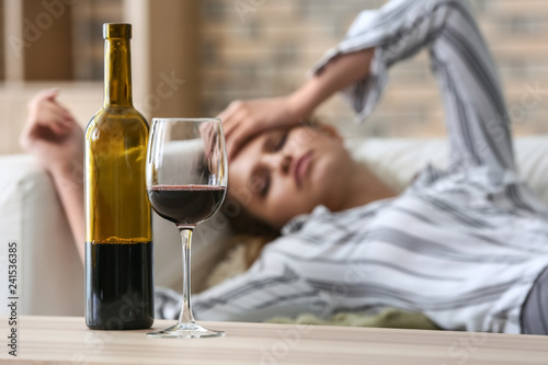 Glass and bottle of wine on table of drunk woman