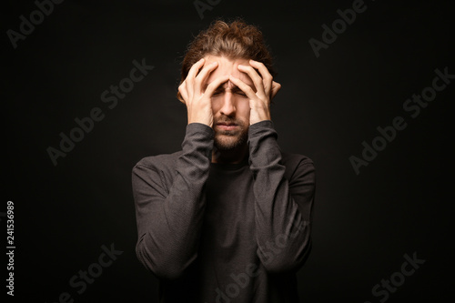 Fotografiet  Young man suffering from headache on dark background
