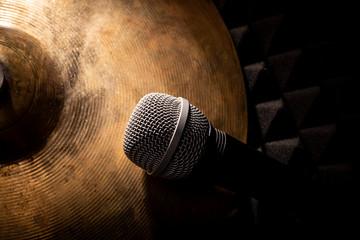 Mikrofon. Talerze perkusji w kompozycji z mikrofonem.