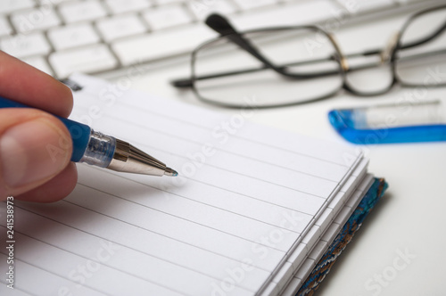 closeup of hand of man writing with blue pen on spirales notebook on white desk background