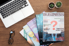 Top View Of Laptop, Business Magazines, Potted Plants And Glasses On Wooden Tabletop
