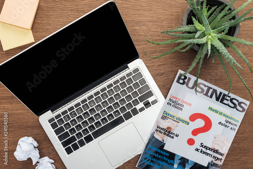 Fototapeta top view of laptop, business magazine and potted plant on wooden tabletop