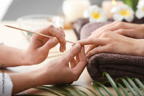 In de dag Manicure Young woman undergoing spa manicure treatment in beauty salon