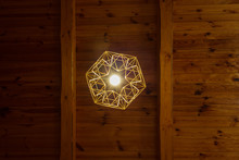 The Ceiling Lamp Is Made Of Straw. Hanging On The Background Of A Wooden Ceiling. Bottom View