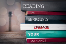 """Pile Of Books With Text Saying """"Reading Can Damage Your Ignorance"""""""