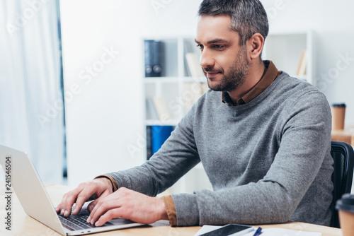 Spoed Foto op Canvas Wanddecoratie met eigen foto handsome smiling bearded businessman working with laptop in office