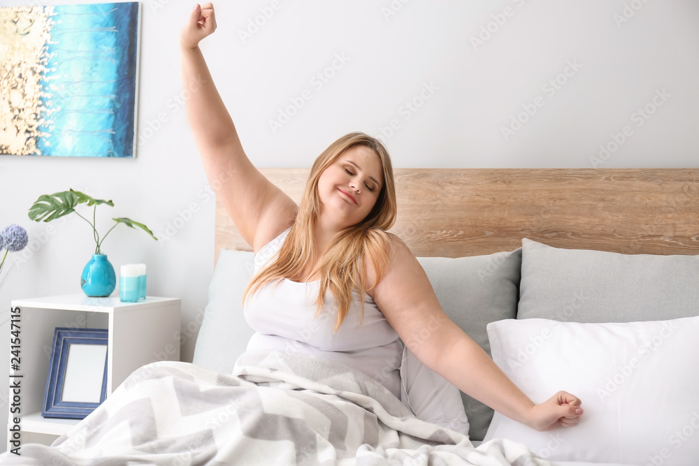 Fototapeta Beautiful plus size girl sitting on bed in morning. Concept of body positivity