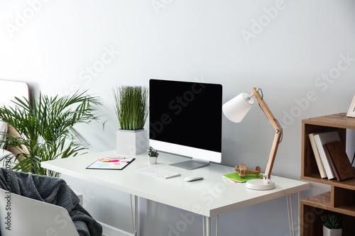 Fotografía  Stylish workplace with modern computer near light wall