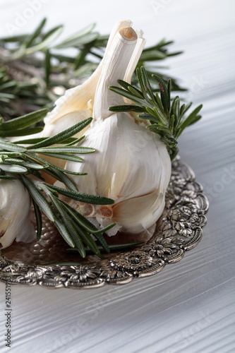 Rosemary and garlic on a wooden table.