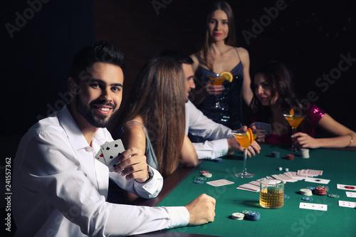 Group of people playing poker in casino Fototapeta