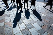歩く人々と長い影