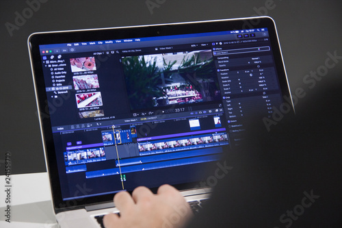 Obraz Video editing with laptop. Professional editor adding special effects or color grading footage for commercial film or movie. - fototapety do salonu