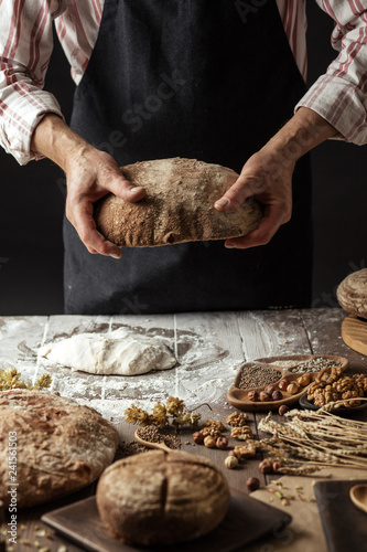 Fotografía Close up of male baker hands holding freshly baked organic bread with a variety