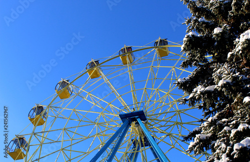 Foto  Ferris wheel with cabins closed in winter sunny weather
