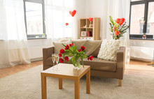 Valentines Day, Holidays And Interior Concept - Two Glasses Of Champagne And Red Flowers On Table In Living Room Or Home Decorated With Heart Shaped Balloons