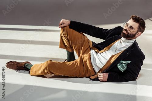 Spoed Foto op Canvas Wanddecoratie met eigen foto handsome stylish bearded man in glasses lying on floor