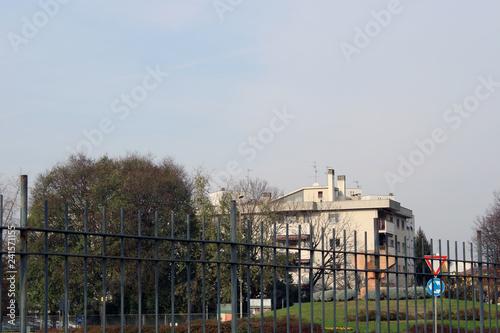 Inferriata metallica con palazzo albero frondoso e simboli stradali Canvas Print