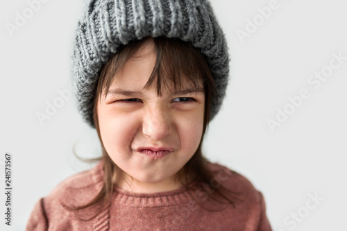 Fotografía  Studio closeup portrait of cute unhappy little girl with grumpy emotion in the winter warm gray hat, wearing sweater isolated on a white studio background