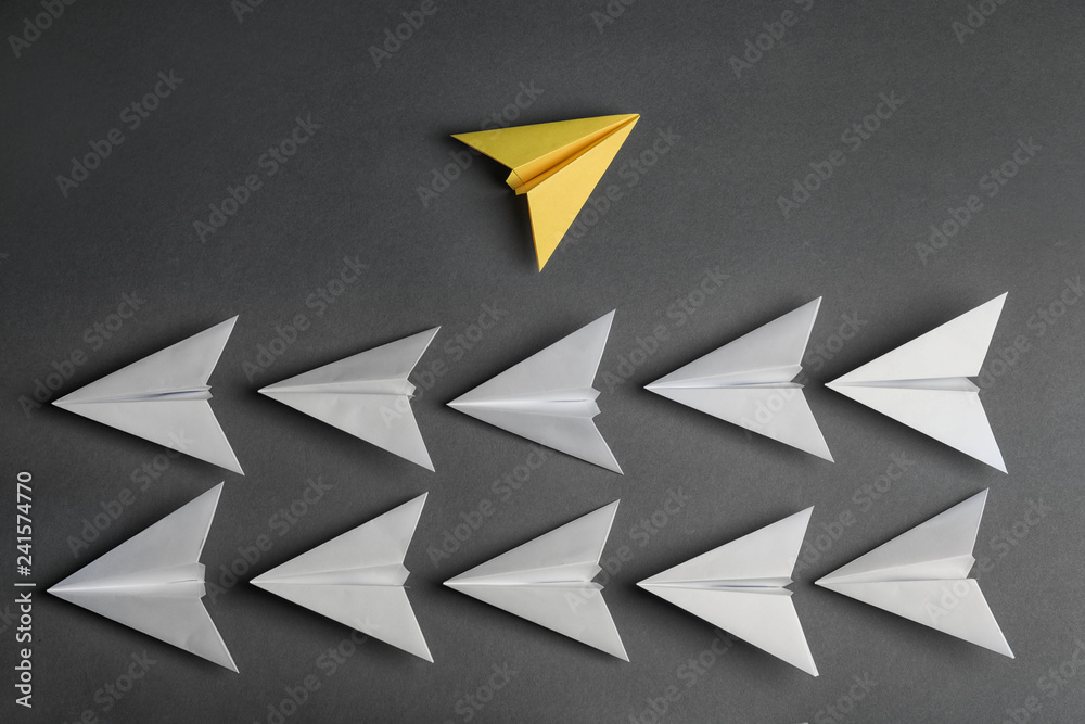 Fototapeta Different color paper plane flying away from others on dark background, top view