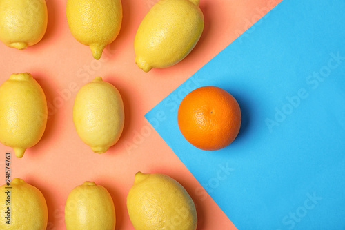 Obraz Orange in front of lemons on color background, top view. Be different - fototapety do salonu