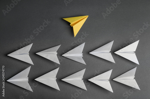 Fotografie, Obraz  Different color paper plane flying away from others on dark background, top view