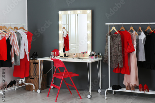 Photo Stylish room with dressing table, mirror and wardrobe racks