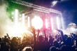 canvas print picture - Young people dancing and having fun in new year's eve festival party outdoor - Crowd with hands up celebrating concert event - Focus on center hand with yellow background flare - Fun and youth concept