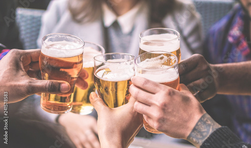 Fotografia  Group of friends enjoying a beer glasses in brewery english pub - Young people c